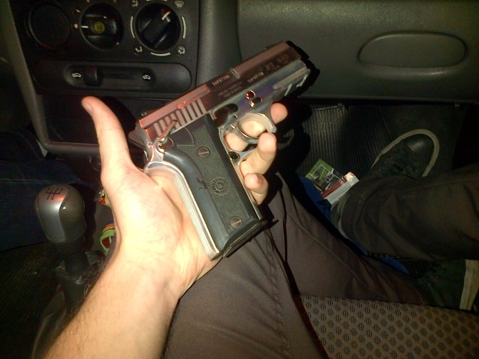 Police-officer's handgun in the car on the way to the night-club
