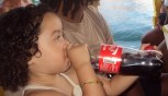 Little Brazilian girl drinking a full bottle of Coca-cola
