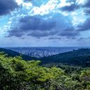 The view of the city of Belo Horizonte, its skyscrapers hidden within a lush valley of green trees, as a storm gathers overhead