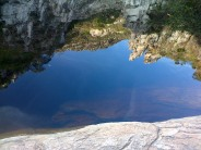 The water is so clear and calm you can see the rocks at the bottom