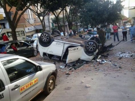 Car landed flipped upside down after smashing through multi-storey car-park wall.
